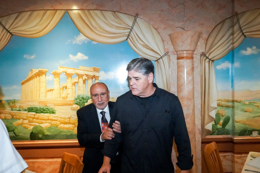 """Sean Hannity, notorious conserva- tive commentator and confidant of Trump, with the owner of Carmela's, an Italian restaurant Hannity used to frequent as a teenager. Hannity is one of the most popular and controver- sial TV hosts in the country. He has supported waterboarding and other forms of torture, equated the Qur'an with Mein Kampf, warned of sharia law coming to the United States, de- nied climate change as """"phony sci- ence from the left,†claimed we won the Iraq War despite """"the Democrats' efforts and attempts at preventing vic- tory,†advocated that Trump """"bomb the hell out of Iran,†and promoted conspiracy theories about Hillary Clinton and Barack Obama. In our photo shoot, he asked what kind of work I did, and I mentioned Palestine and Israel. He asked if I knew """"Bibi†(the nickname of Benjamin Netanya- hu, the prime minister of Israel). I said no. He asked what I thought about Bibi's policies. I said I didn't agree with them and that it was way past due for good faith negotiations to establish a Palestinian state. He looked at me with amusement and pity and said, """"Did you know the Pal- estinian Authority gives money to the families of dead terrorists? That's state-sponsored terrorism. You don't negotiate with terrorists.†Perplexed by what that point had to do with the conversation at hand, I tried to have a more analytical discussion of the history and conditions of violence in the region, but he stopped engaging. Franklin Square, New York.USA. 2017."""