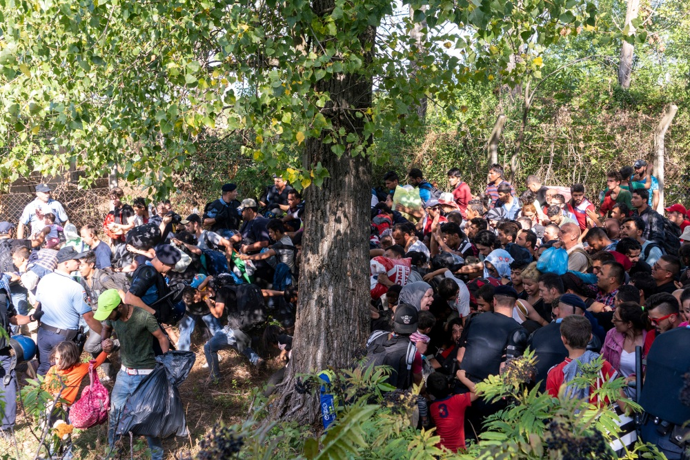 Refugees crash through police lines in Tovarnik, Croatia, during the height of the refugee crisis. They had arrived en masse during the pre- vious days when Hungary shut its borders. The Croatian authorities, unsure how to deal with the sud- den influx, kept them penned up in a train station in the sweltering late summer heat. Lacking food and wa- ter, the refugees protested, ultimately pushing through police lines. The Croatian authorities set up another cordon, but eventually relented and arranged for a fleet of buses to carry them to Zagreb so they could contin- ue their journey to Western Europe. Some Croatian police seemed indif- ferent to the refugees' desperation, but others mentioned being refugees themselves as children during the Balkan wars of the early '90s and extended acts of kindness when they could. The refugees were exhausted and many annoyed with the constant media presence. As the police lines imploded, I was admonished in En- glish several times that the media should stop portraying them as a de- fenseless, dehumanized horde. Owing to decades of anti-Islam propagan- da, many townspeople on the border seemed to regard the refugees with deep suspicion.Tovarnik. Croatia. 2015.