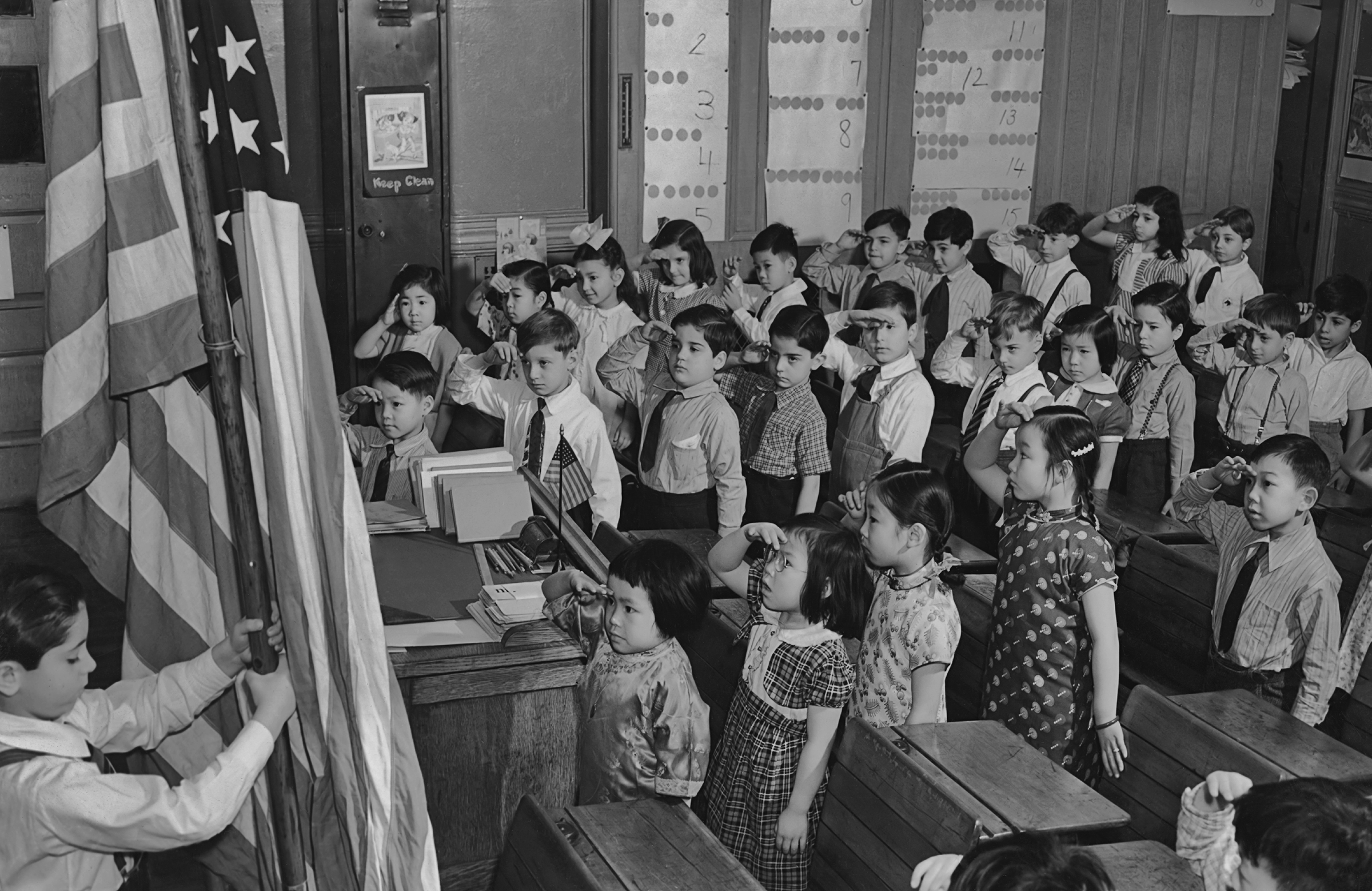 A group of children saluting the American flag at a school in the Chinatown area of Manhattan circa 1960.