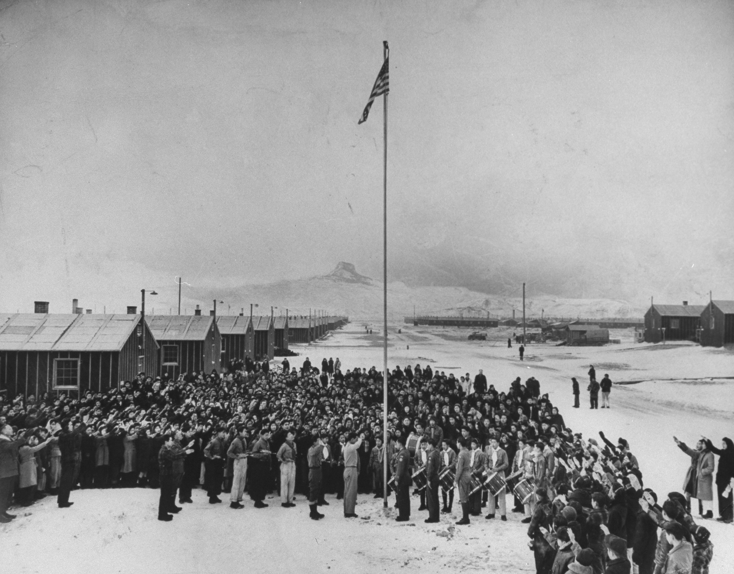 Nisei Japanese-Americans participating in a flag saluting ceremony at a relocation center in forced internment during WWII, 1942.