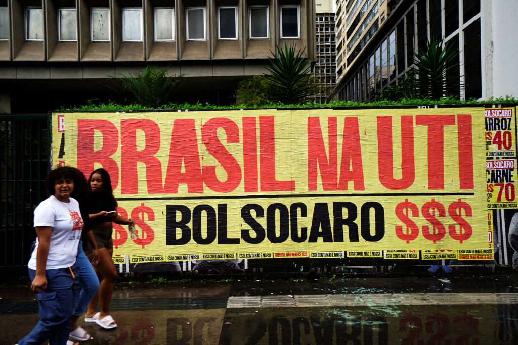 People walk in front of a banner that reads 'Brazil in the ICU, BolsoOverpriced' in reference to Brazilian president Jair Bolsonaro and the high prices of basic goods during the outbreak of COVID-19 in Sao Paulo, Brazil March 9, 2021.