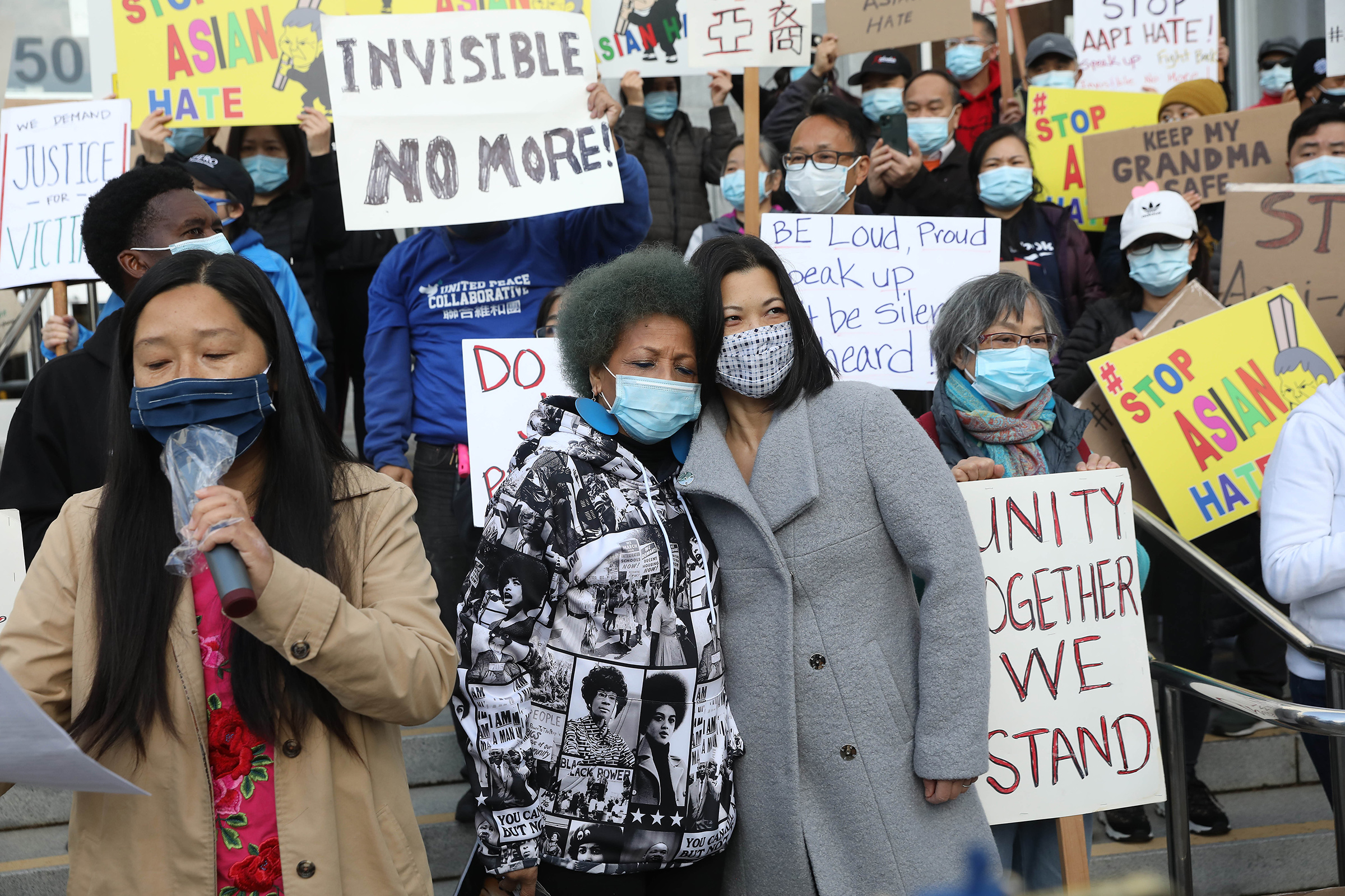 Mattie Scott (center, left to right), founder and Executive Director of Healing 4 Our Families & Our Nation and Nancy Tung, public safety advocate, hold each other as they rally with demonstrators rallying in front of the Hall of Justice as they demand justice for Vicha Ratanapakdee on March 22 in San Francisco