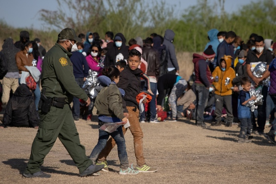 A U.S. Border Patrol Agent escorts two asylum-seeking unaccompanied minors from Central America as others take refuge near a baseball field after crossing the Rio Grande river into the United States from Mexico on rafts, in La Joya, Texas, on March 19