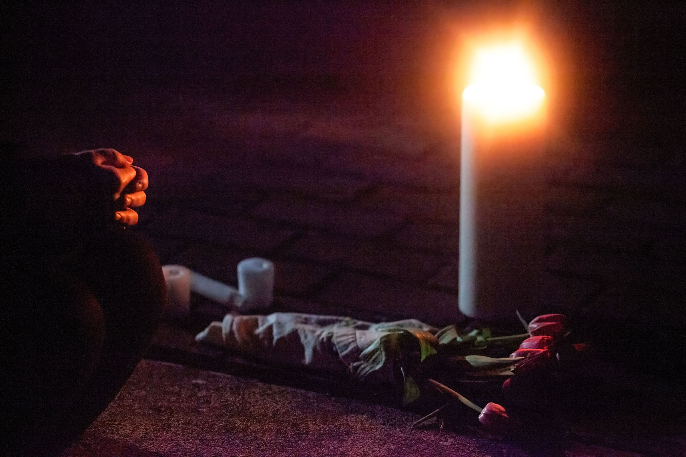 An attendee of a vigil kneels in front of a candle and flowers in memory of those who were killed in the shooting in Atlanta, on March 20, 2021.