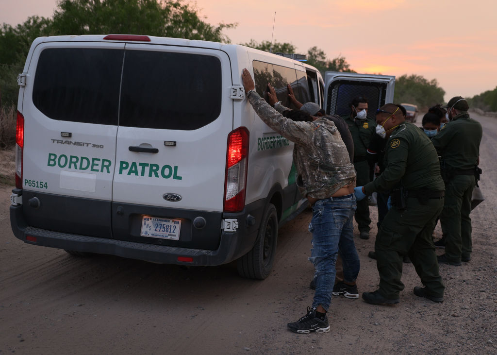 U.S. Border Patrol agents process a group of people they caught crossing the border from Mexico on March 27, 2021 in Penitas, Texas.