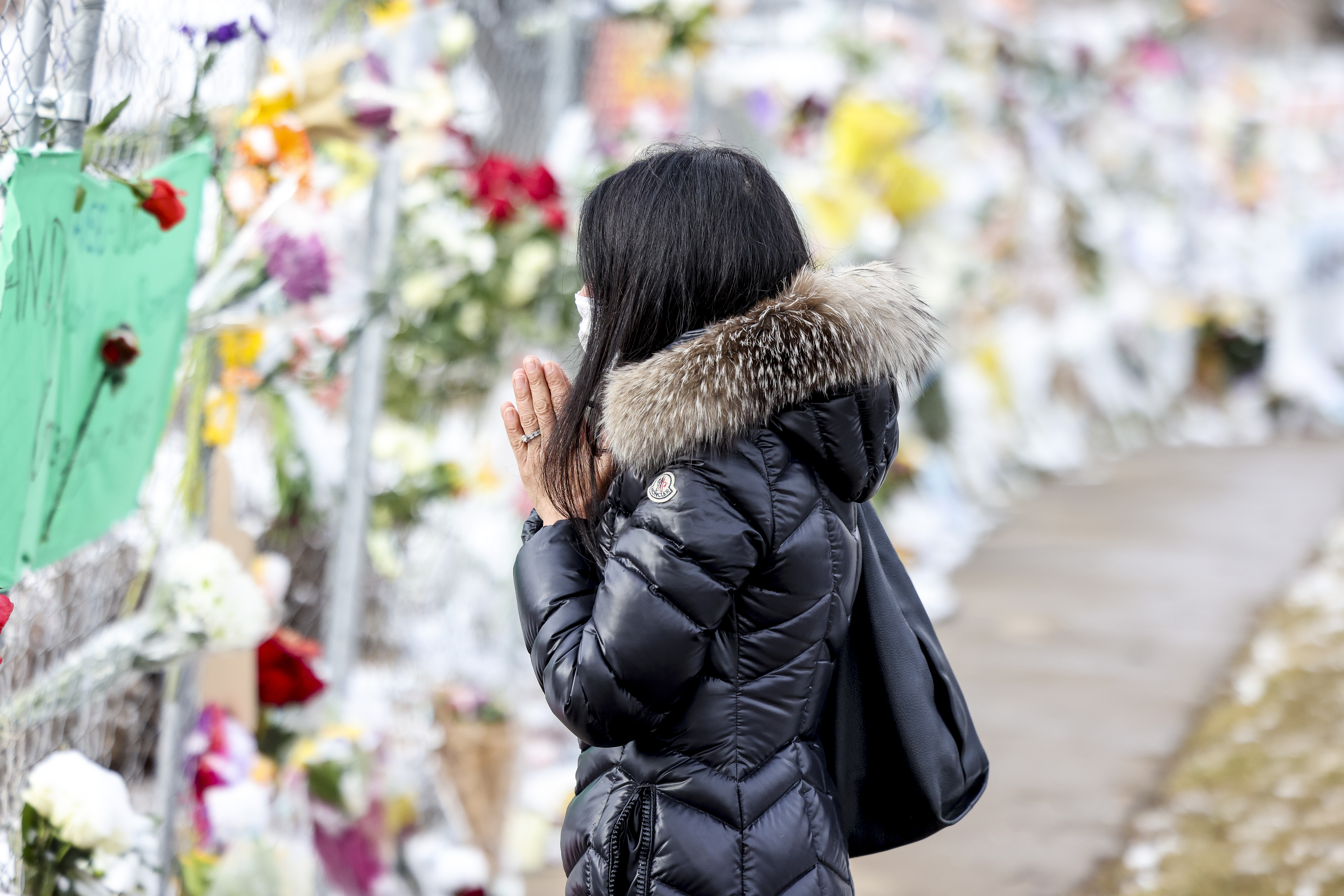 Takoua Debeche prays at a makeshift memorial for the victims of a mass shooting outside a King Soopers grocery store on March 24, 2021 in Boulder, Colorado.