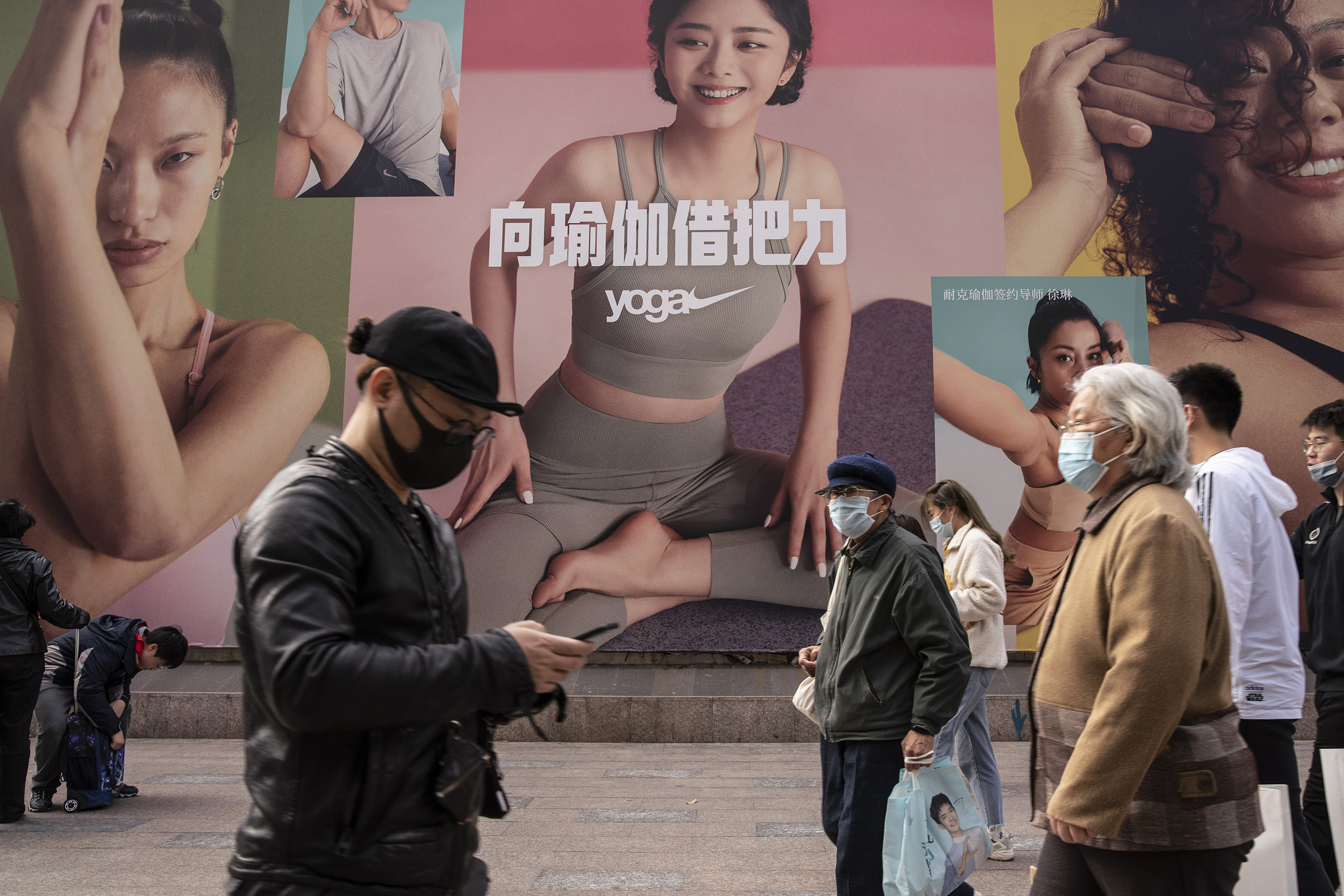 Pedestrians walk past a Nike advertisement in Shanghai on March 26. China this week has pushed a campaign to boycott Western retailers after the U.S., U.K., Canada and the E.U. imposed sanctions over human-rights abuses against ethnic minority Uyghurs in Xinjiang.
