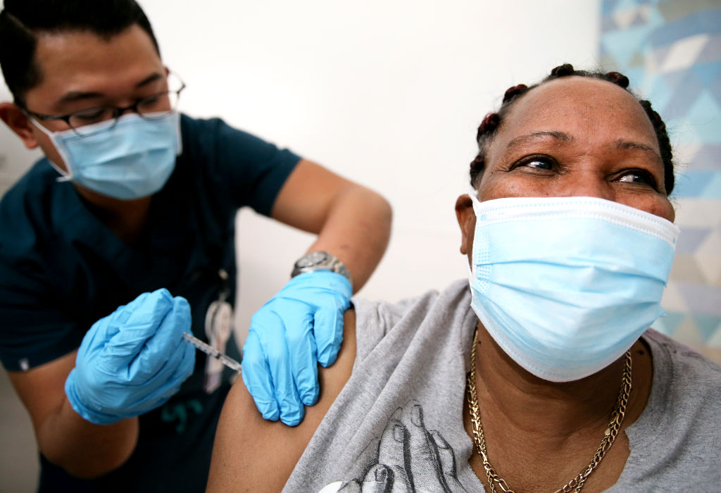 Lorraine Harvey, an in-home care worker, receives her first dose of the COVID-19 vaccine from registered nurse Rudolfo Garcia at a clinic at Martin Luther King Jr. Community Hospital in South Los Angeles on February 25, 2021 in Los Angeles, California.