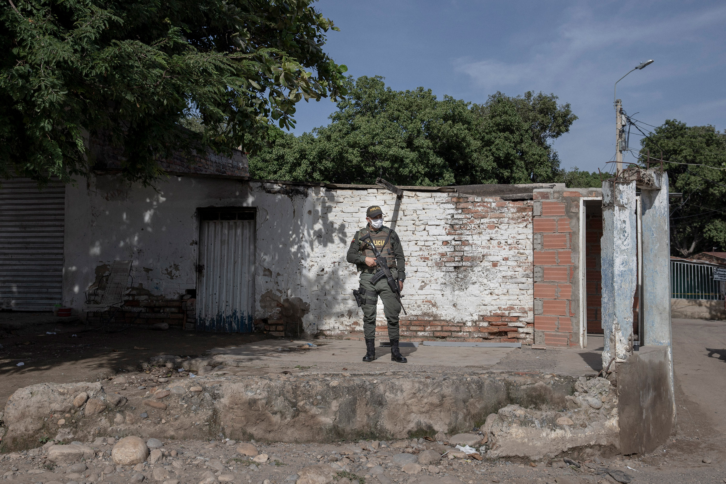 Un oficial de policía colombiano se encuentra en la entrada de un cruce fronterizo ilegal.