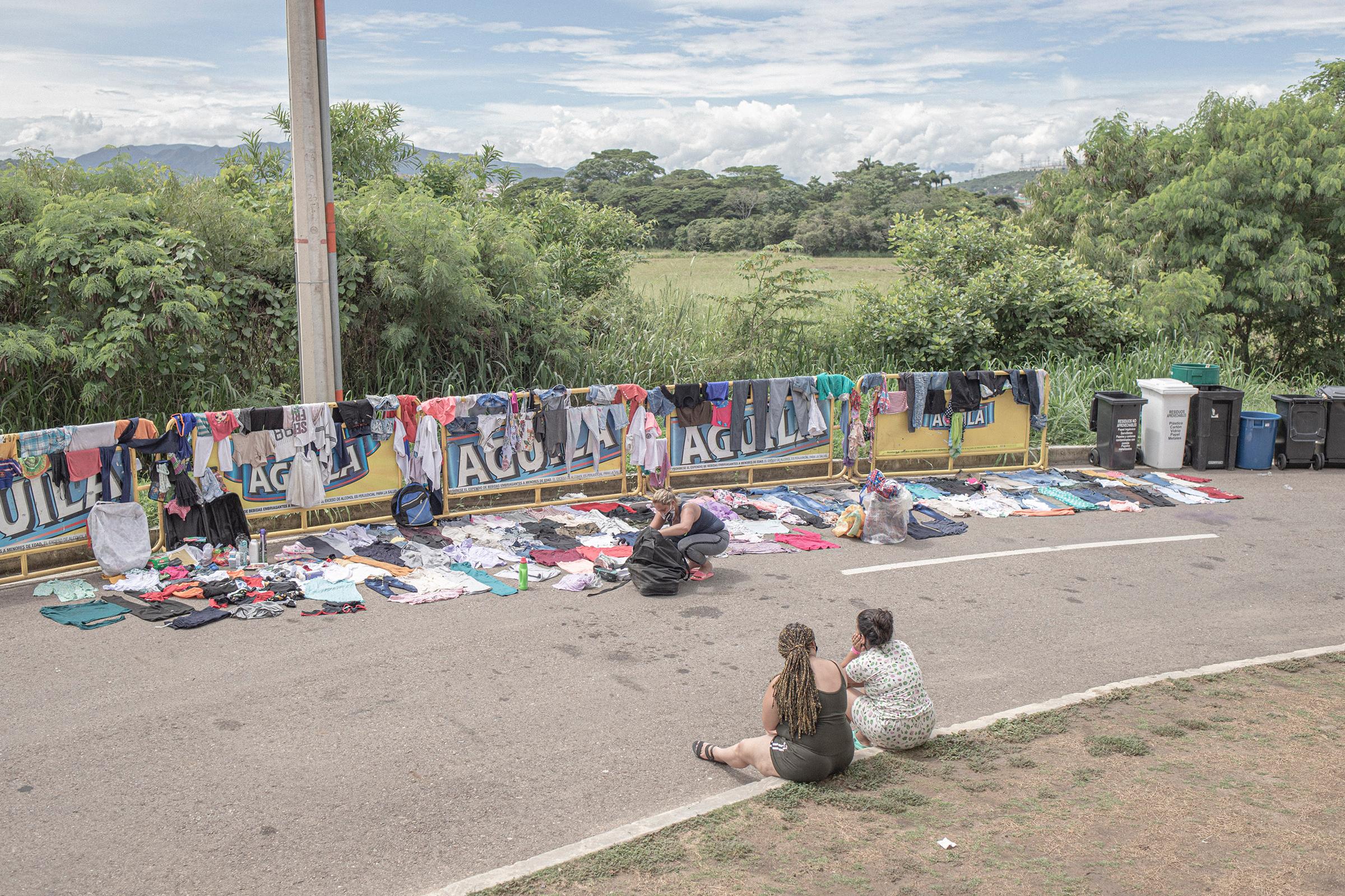 En un campo de retorno de migrantes en C كوك cuta, Colombia, mujeres venezolanas secan la ropa.