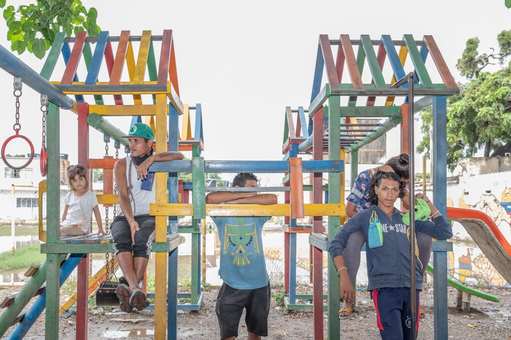 A group of Venezuelans at a playground in a park on the border.