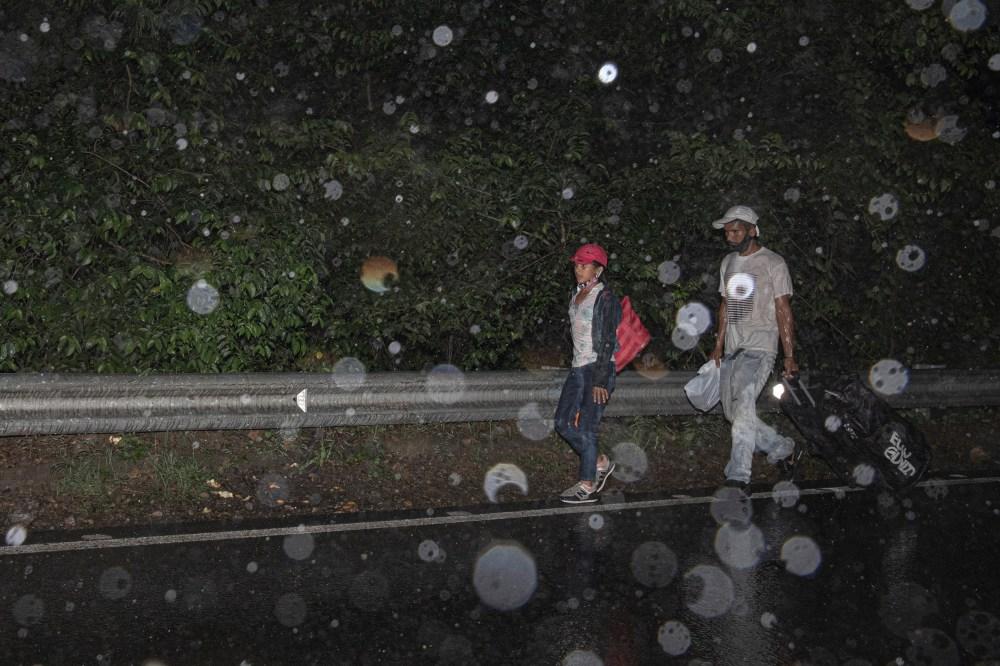 Venezuelan migrants walk along a highway in Norte de Santander, Colombia, under heavy rain.