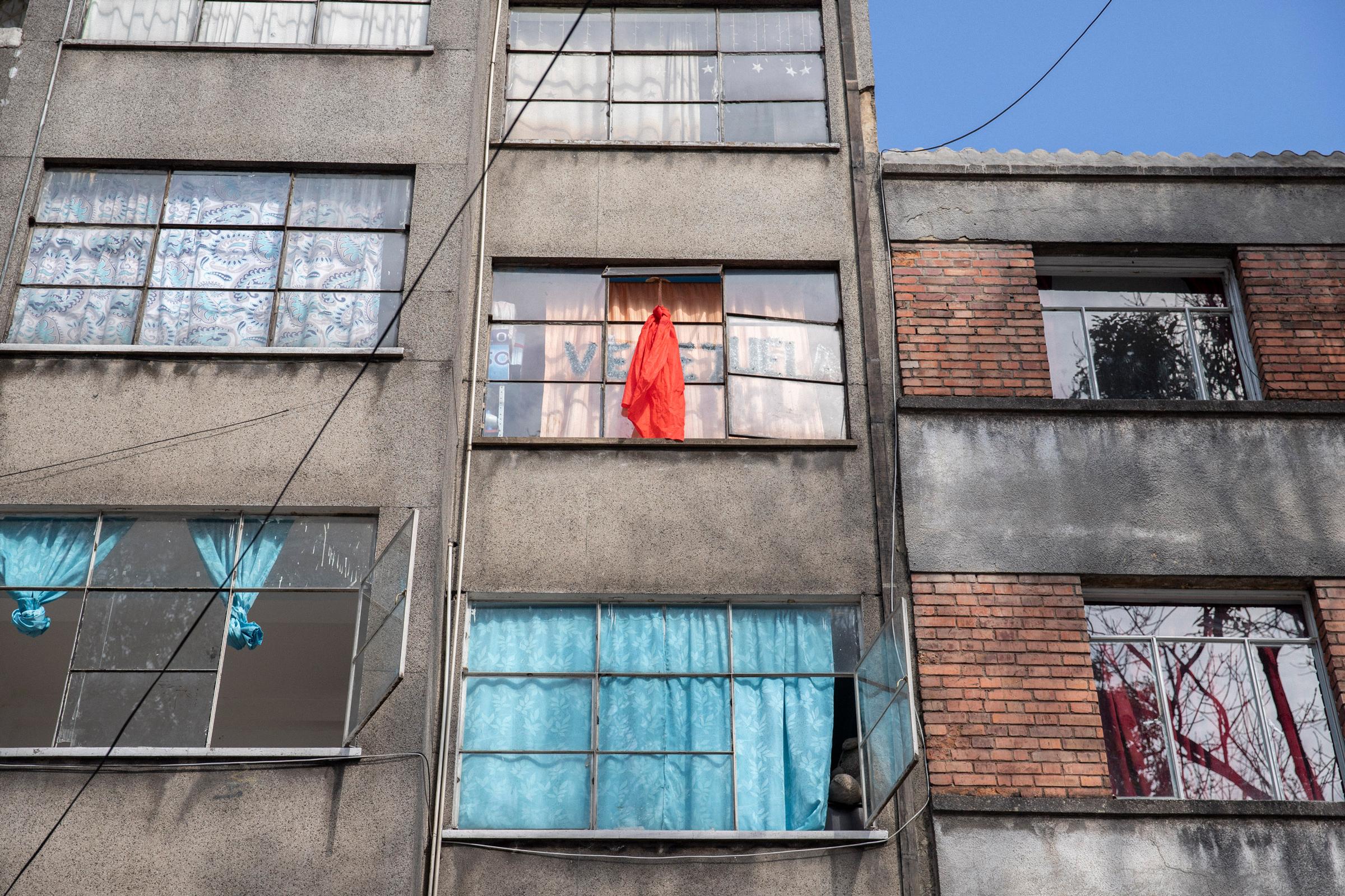 Un edificio en Bogotá que alberga inmigrantes venezolanos.  Los pasajeros que necesitan comida desesperadamente colocan un paño rojo en sus ventanas.