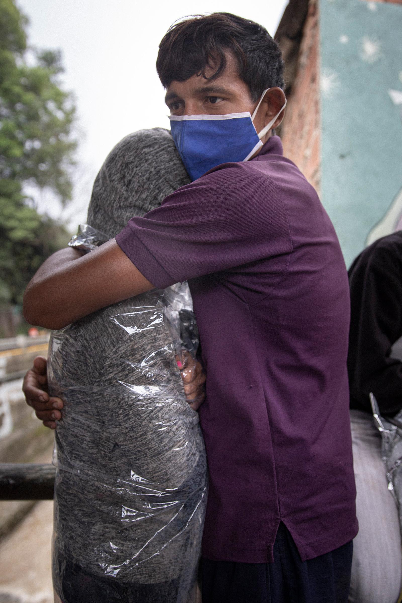 Johnmier Briceño y su novia se abrazan mientras se esconden de la lluvia en Pamplona, Colombia.
