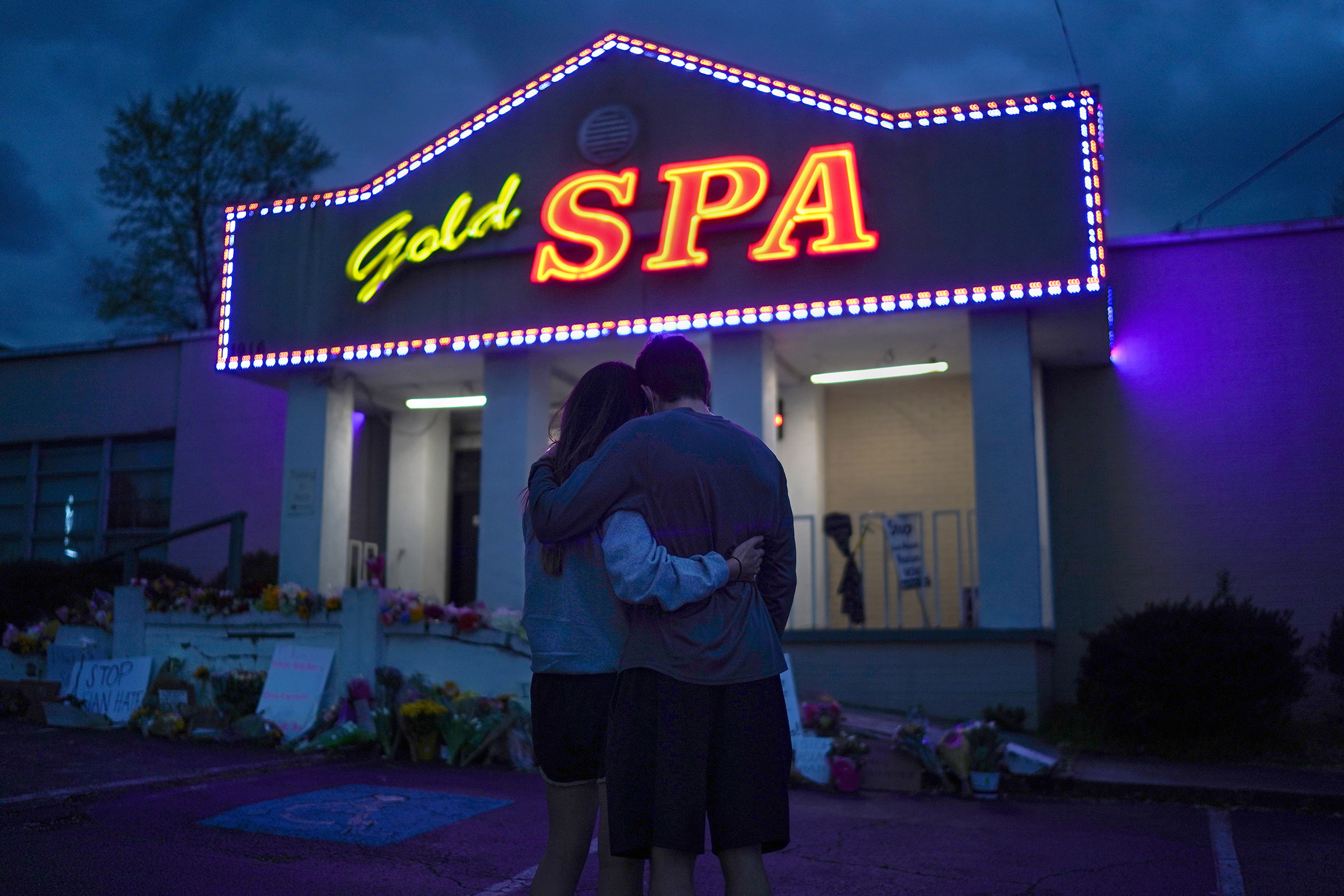 Cynthia Shi and her boyfriend, Graham Bloomsmith, embrace outside Gold Spa, one of the three Atlanta-area businesses where a gunman fatally shot eight people, including six women of Asian descent.