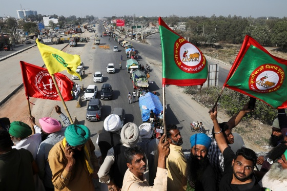 Farmers cheer and wave flags near Kundli border in Haryana, India, as more tractors arrive from Punjab to participate in the ongoing farmers' protest at Singhu border to mark the 100th day of demonstrations against the farm laws on March 6