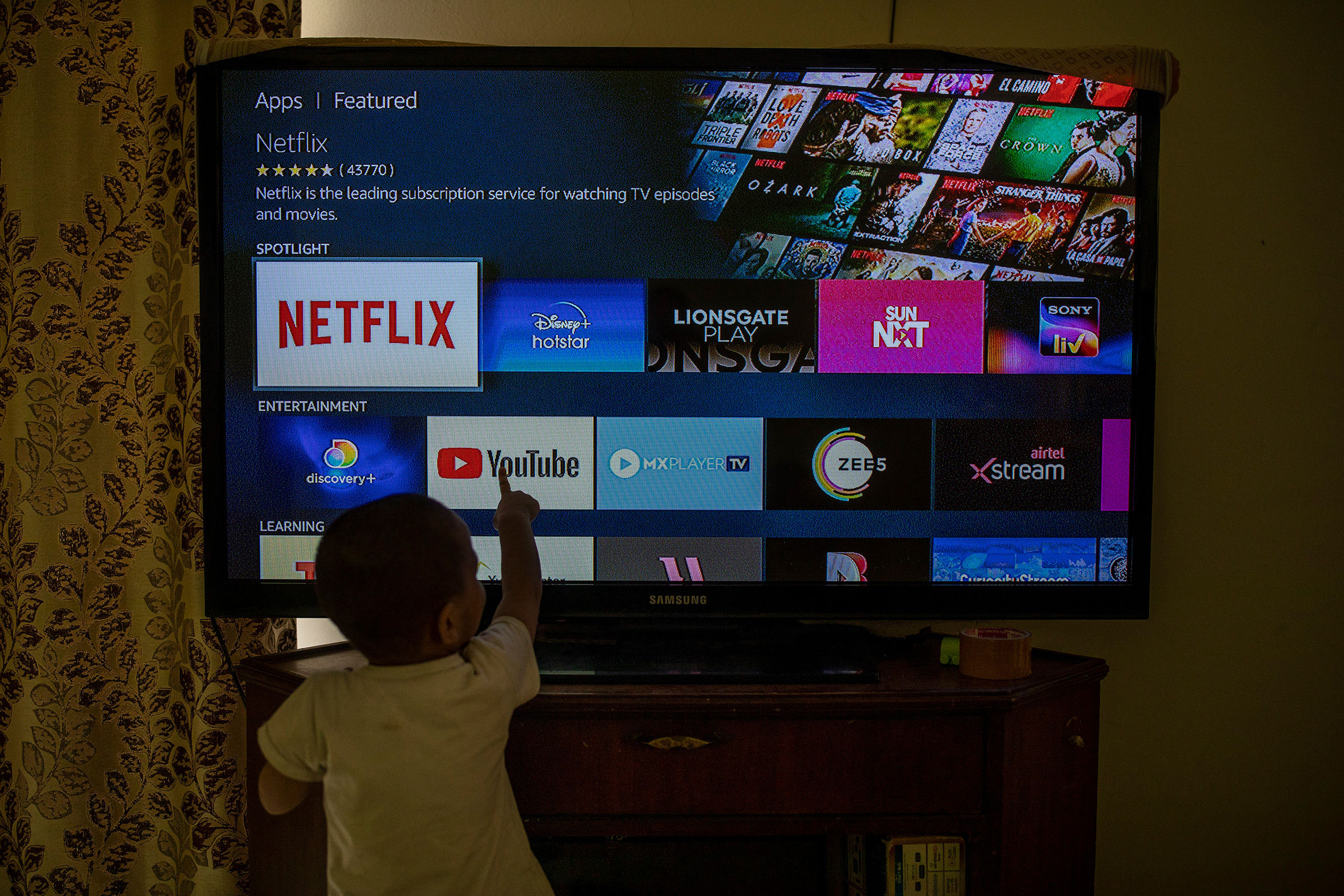 A child touches a TV screen displaying OTT streaming apps at his home in New Delhi, Feb. 25. India has rolled out new regulations for social media companies and digital streaming websites to make them more accountable for the online content shared on their platforms.