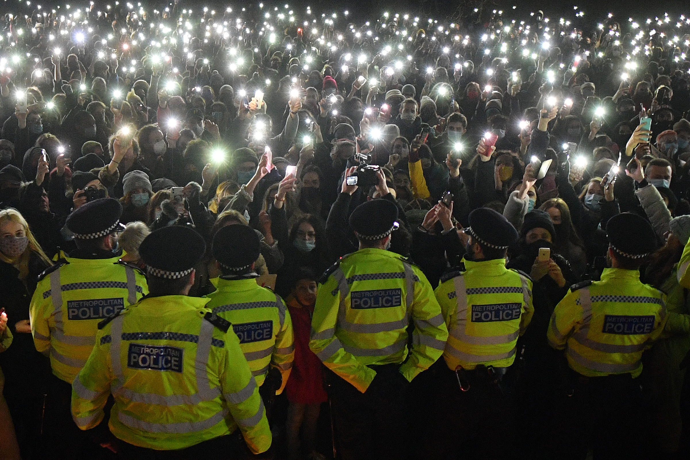 Well-wishers, gathered for a planned vigil for Sarah Everard in Clapham Common, south London, turn on their phone torches as the event was cancelled after police outlawed it due to Covid-19 restrictions on March 13