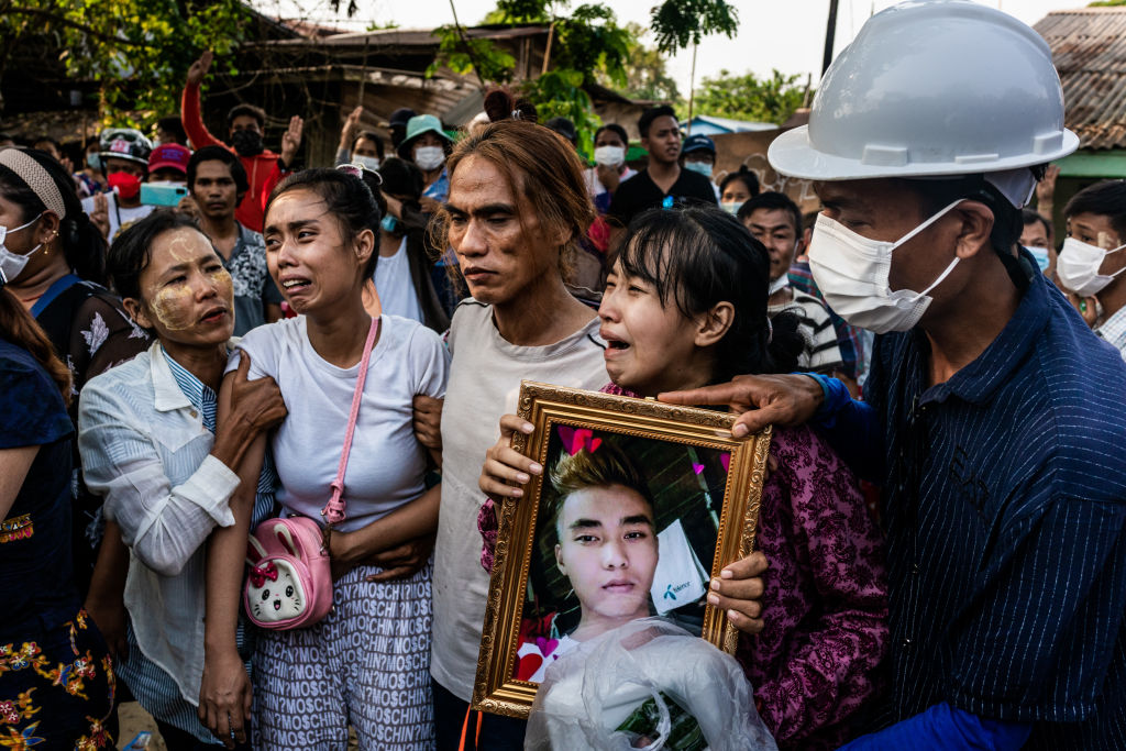 The wife (2nd from left) and a sister (2nd from right) of Chit Min Thu, 25, who was killed in clashes, cry during his funeral at the family's home in Yangon, Myanmar on March 11, 2021.