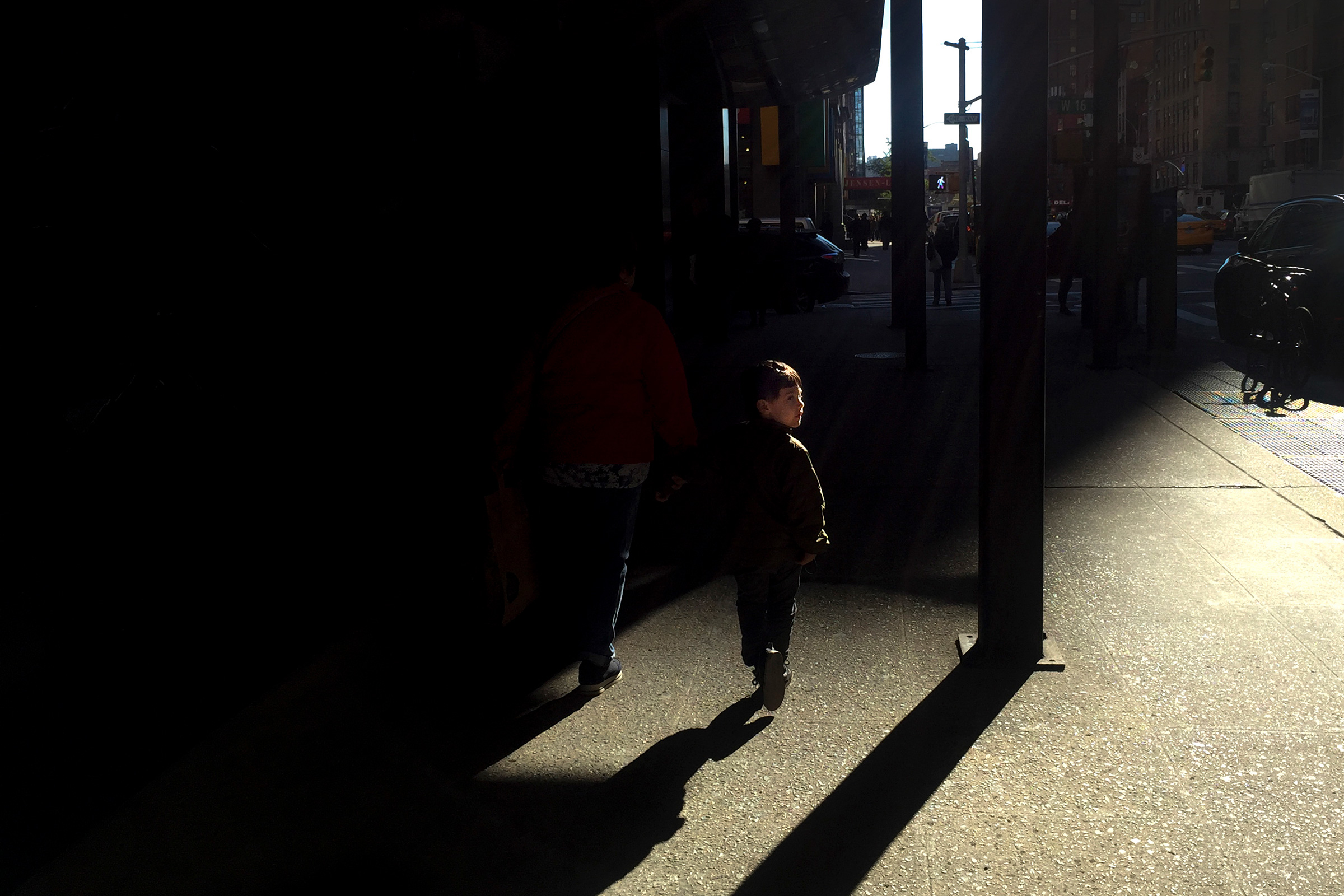 A scene-scape of New York capturing a young boy walking by.