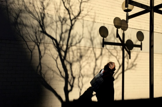 A passerby in New York covered in shadows from a tree.