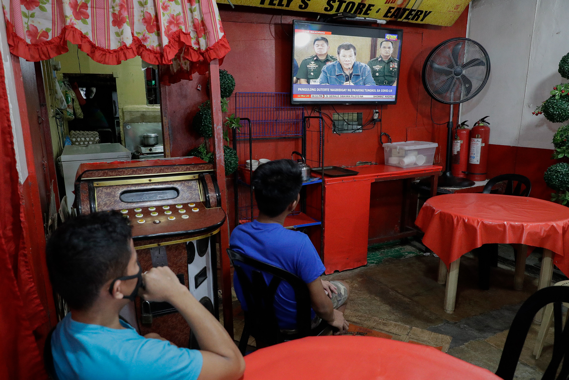 Restaurant workers watch Philippine President Rodrigo Duterte as he delivers a speech on TV about the COVID-19 virus situation in metropolitan Manila on March 12, 2020