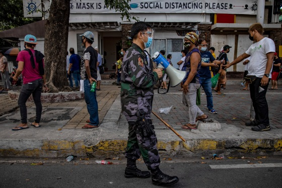 A police officer reminds homeless people to practice social distancing as they queue to receive free meals distributed by members of the Society of the Divine Word (SVD) on Dec. 15, 2020 in Manila.