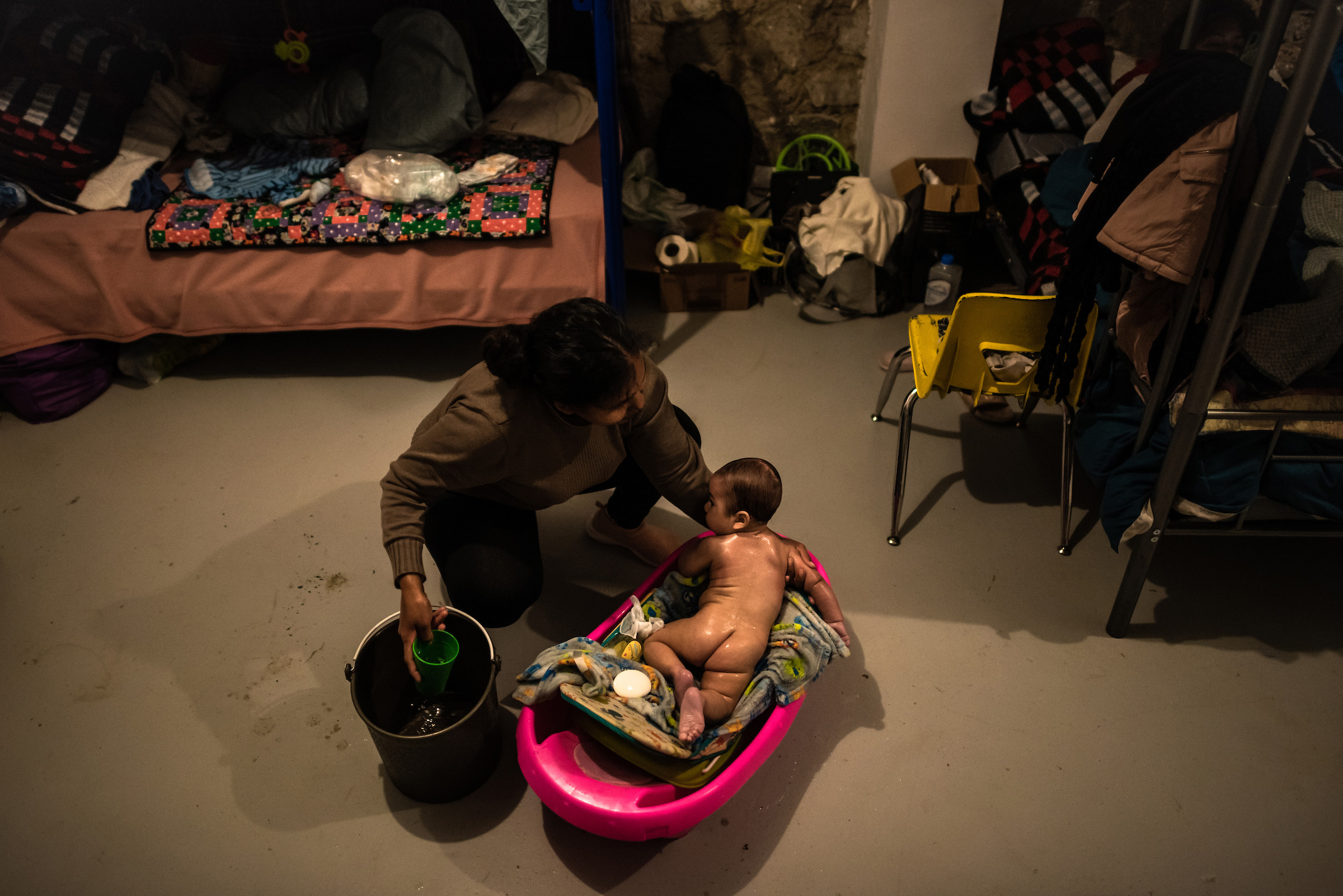 A mother from El Salvador bathes her baby.