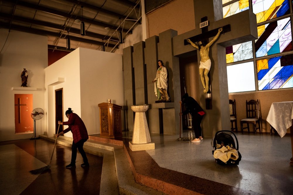 Migrant women mop the sanctuary floors of the San Juan Apóstol Evangelical Parish. The Parish built living quarters on the side of their church to shelter migrant women who are pregnant or who recently gave birth.