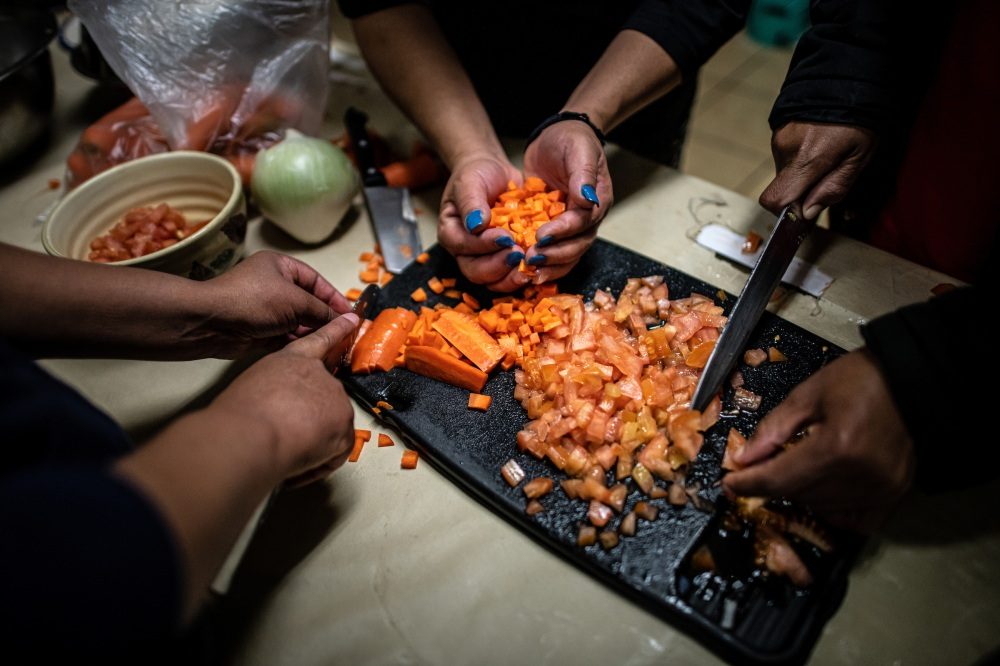 Shelter guests chop carrots while cooking soup together in the kitchen.