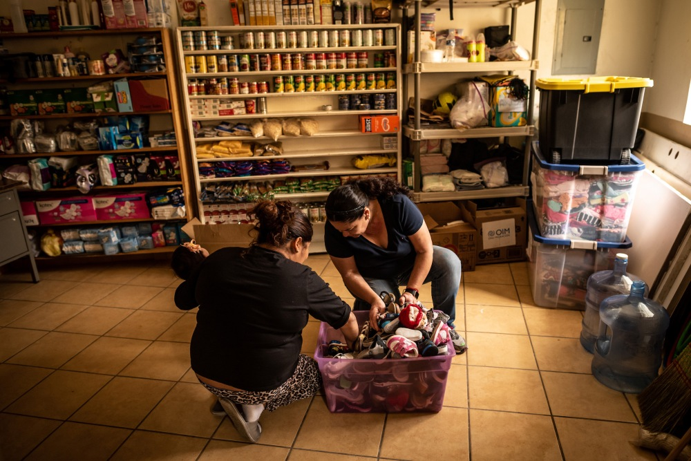 Shelter volunteer Marta Leticia Galarza Gandara, 50, right, helps Isa, 31, find shoes for her baby daughter in a box of donations. Isa is an asylum seeker from Honduras, and has been waiting at the border under MPP since September 2019.