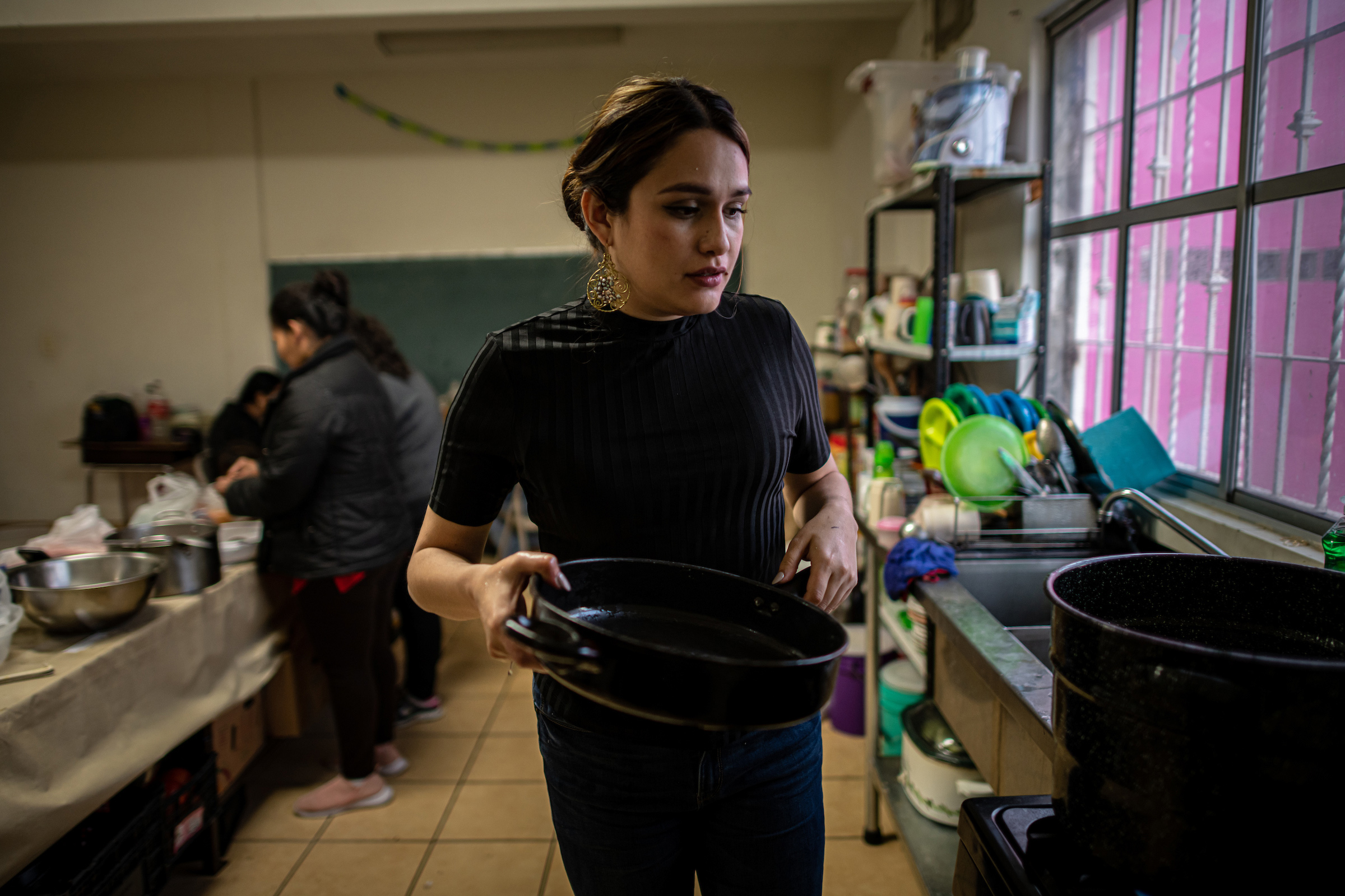 "Shelter coordinator Karina Breceda cooks soup with migrant women in the kitchen. ""When I see my team, they're basically on call 24/7,"" Breceda says. ""There's a lot of peace, and a lot of healing with the work that they're doing."