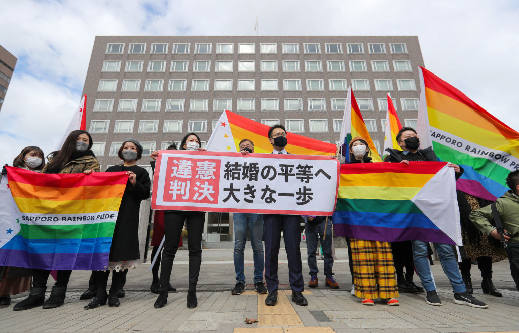 Supporters hold the  unconstitutional decision  flag as they are pleased with the Sapporo District Court's decision that it is unconstitutional to not allow same-sex marriage in Sapporo, Hokkaido prefecture on March 17, 2021.