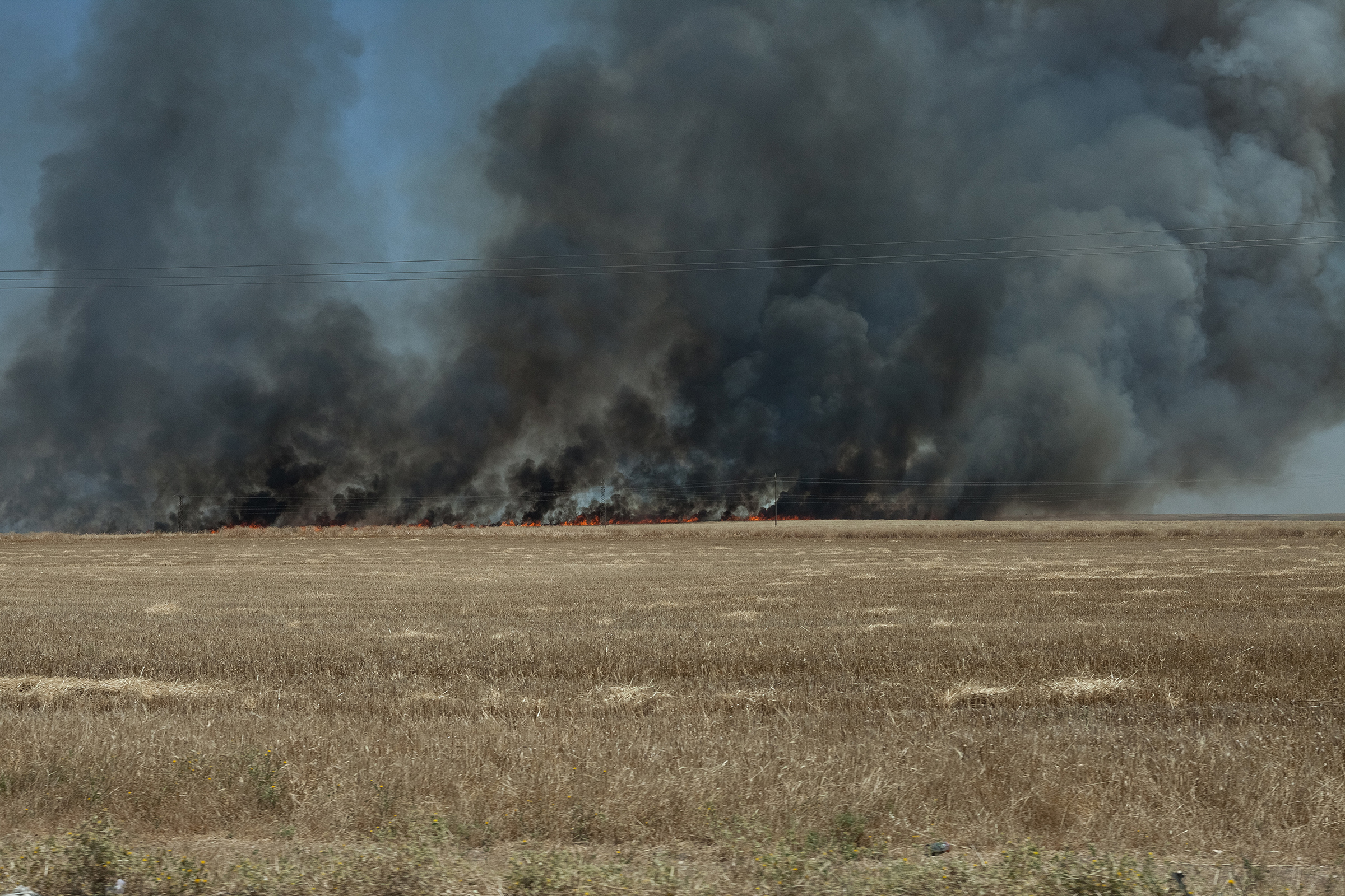 A field burns on the road between Al-Maabadah and Qamishli in June 2019. The dominating rumor among the Kurdish population was the fires were set by ISIS sleeper cells.
