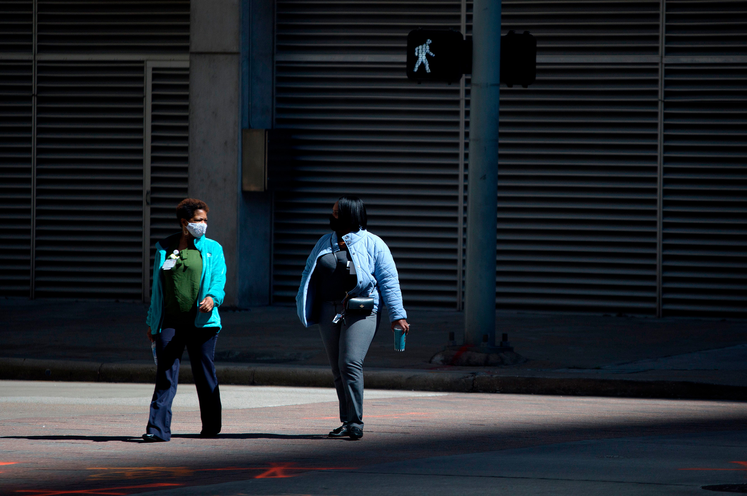 Pedestrians wear masks while walking across a street in downtown Houston, Texas on March 3, 2021.