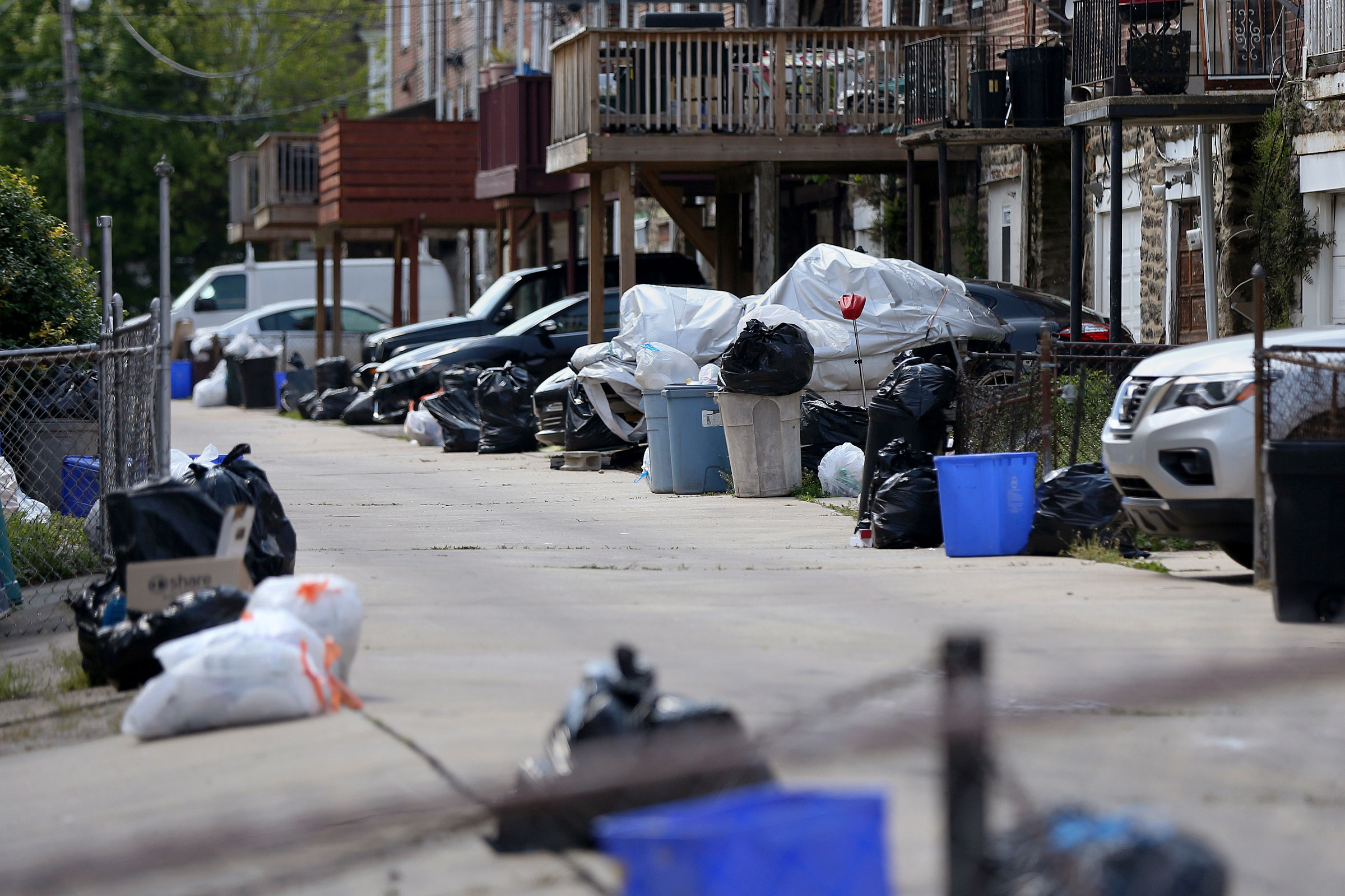 Bags of garbage sit along the street before being picked up in Philadelphia's Ogontz neighborhood on May 13, 2020.
