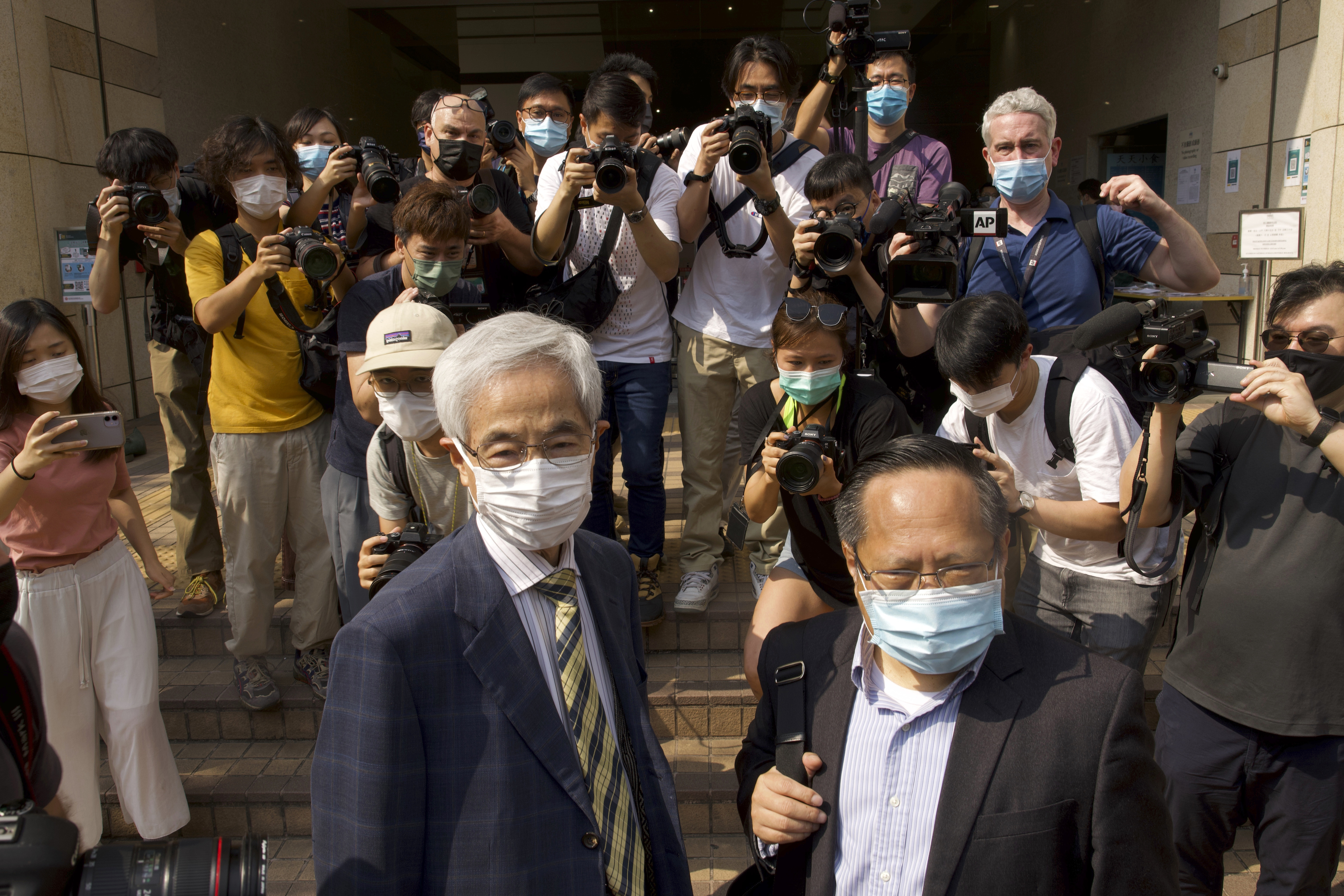 Pro-democracy lawmaker Martin Lee, left, and Albert Ho, right, arrive at a court in Hong Kong Thursday, April 1, 2021.