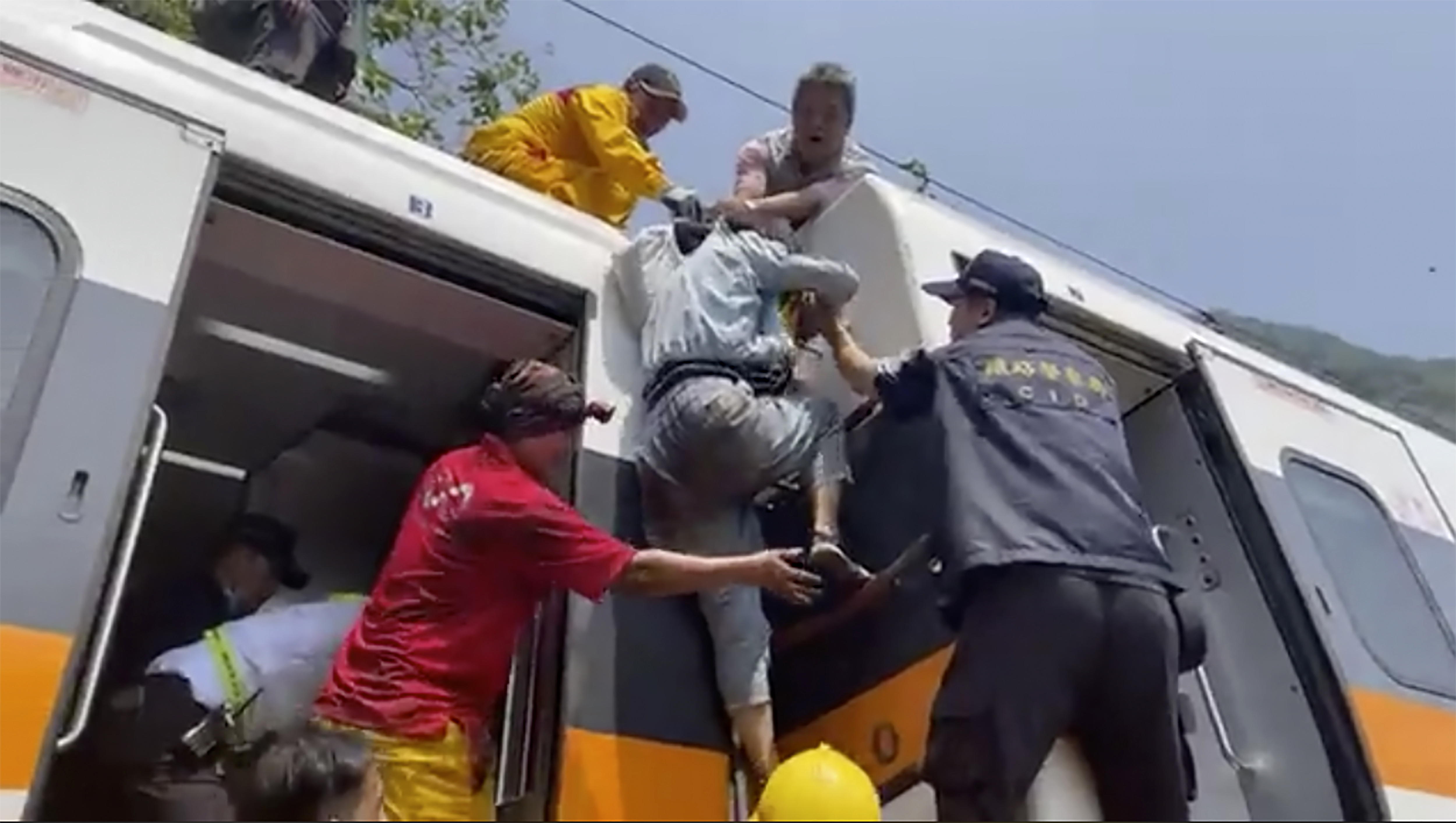 In this image made from a video released by hsnews.com.tw, a passenger, center, is helped to climb out of a derailed train in Hualien County in eastern Taiwan Friday, April 2, 2021.