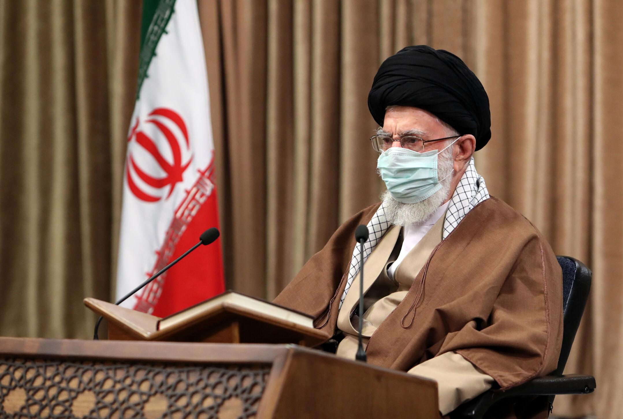 In this picture released by an official website of the office of the Iranian supreme leader, Ayatollah Ali Khamenei, wearing a protective face mask, attends a meeting in Tehran, Iran, Wednesday, April 14, 2021.