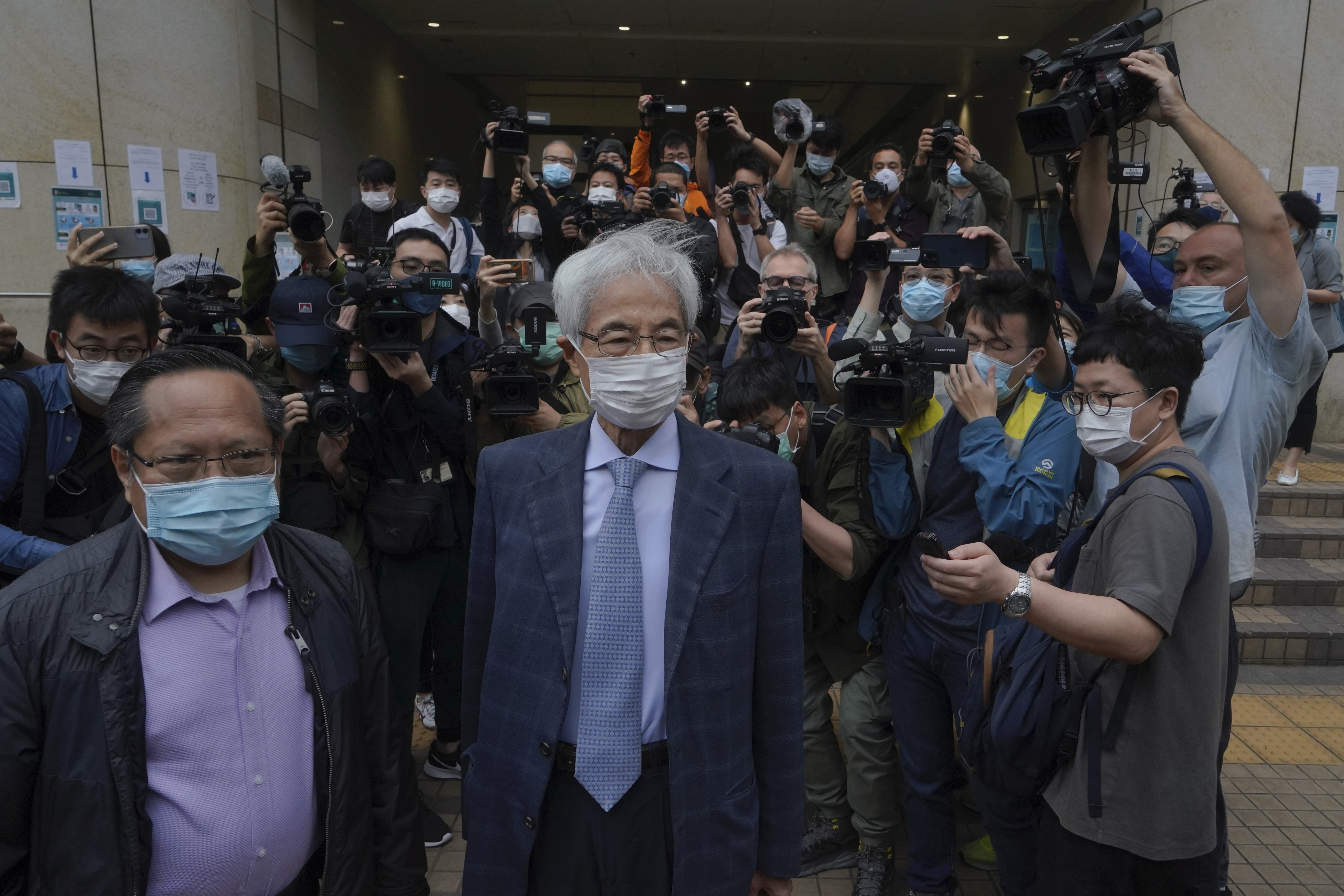 Pro-democracy activists Martin Lee, center, and Albert Ho, left, arrive at a court in Hong Kong Friday, April 16, 2021.