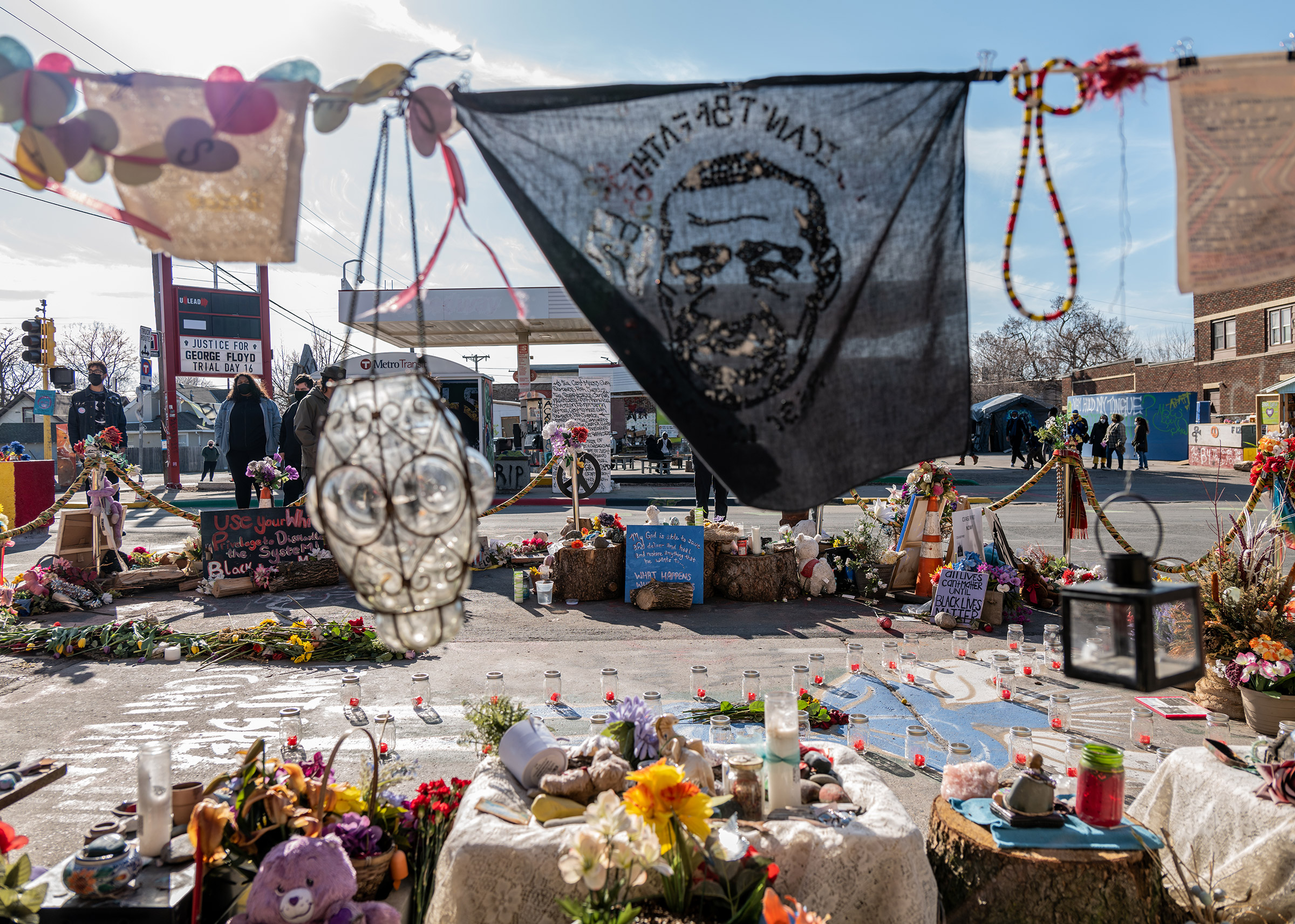 A handkerchief bearing George Floyd's image waves over candles, flowers and other items at the memorials in the square where he was killed in Minneapolis.