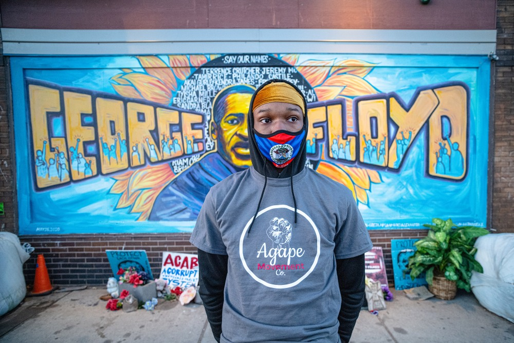 Ljhvonn Waller, 16, stands in front of a mural of George Floyd painted on the east 38th street side of Cup Food, near the intersection where Floyd died and a memorial remains. Waller was preparing to join the members of Agape, a non profit organization of men who live in the community who are trying to prevent and disrupt violence in that Minneapolis area.