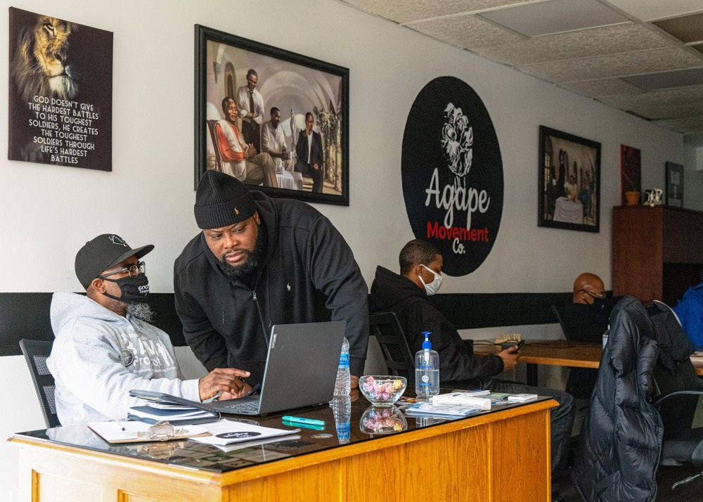 Alfonso Williams (standing) of the group Agape leads a zoom meeting with other members of the group and is seeing here in conversation with Marquise Bowie (seated)