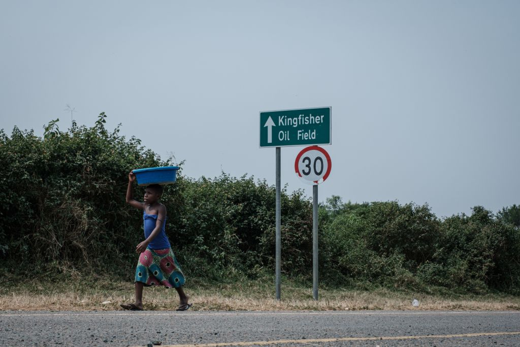 A girl walks past a sign for the Kingfisher oil field in the south-east of lake Albert in Uganda, on Jan. 24, 2020