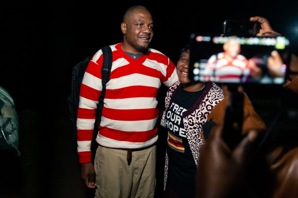 Zimbabwean journalist Hopewell Chin'ono is embraced by a supporter following speaking to the press after his release on bail from Chikurubi Maximum Prison in Harare, on September 2, 2020.