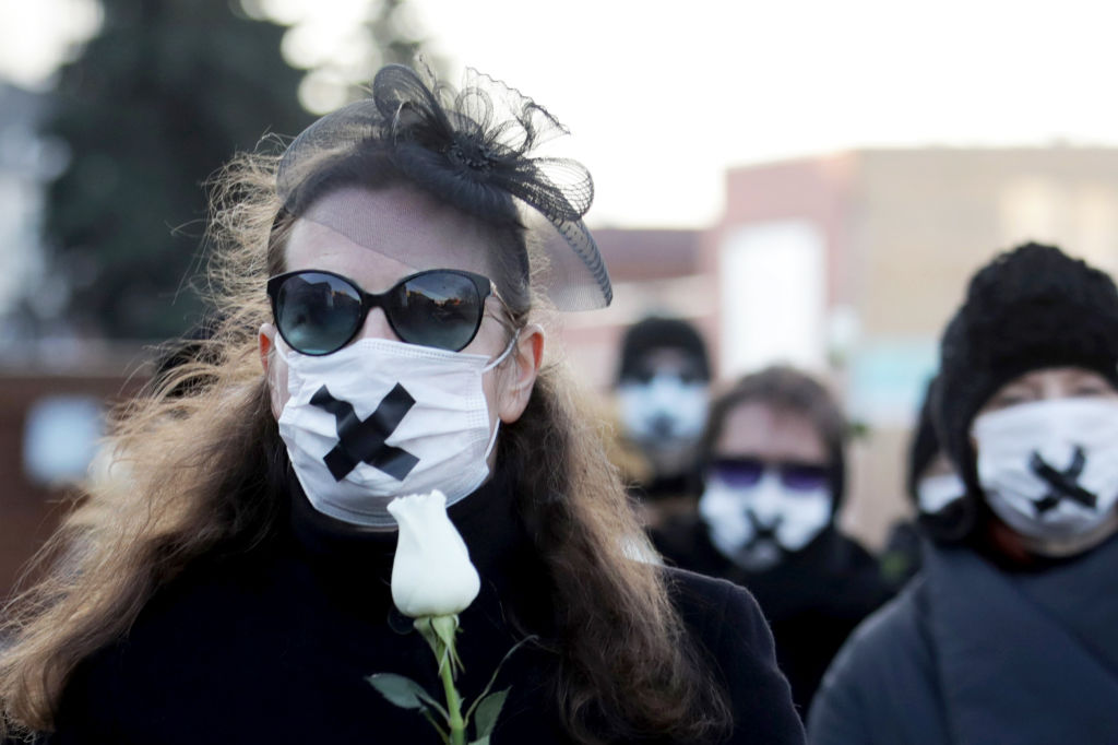 Women wearing black clothing and tape crossed over their mouths hold white roses as they march on March 2, 2021, in Minsk, during a demonstration against the conviction of a doctor and a journalist over the disclosure of medical records of a protester who died after being detained at one of the post-election rallies that swept Belarus last year.