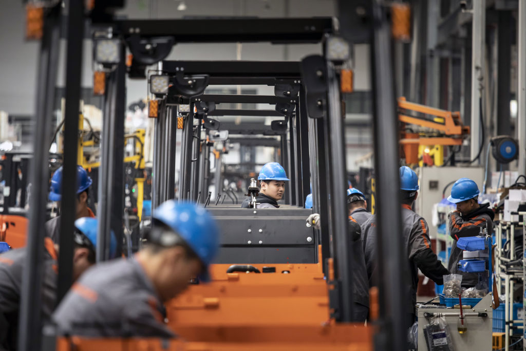 Employees work on a production line for electric forklifts during a media tour at a Noblelift Intelligent Equipment Co. factory in Huzhou, Zhejiang province, China, on Wednesday, April 14, 2021.