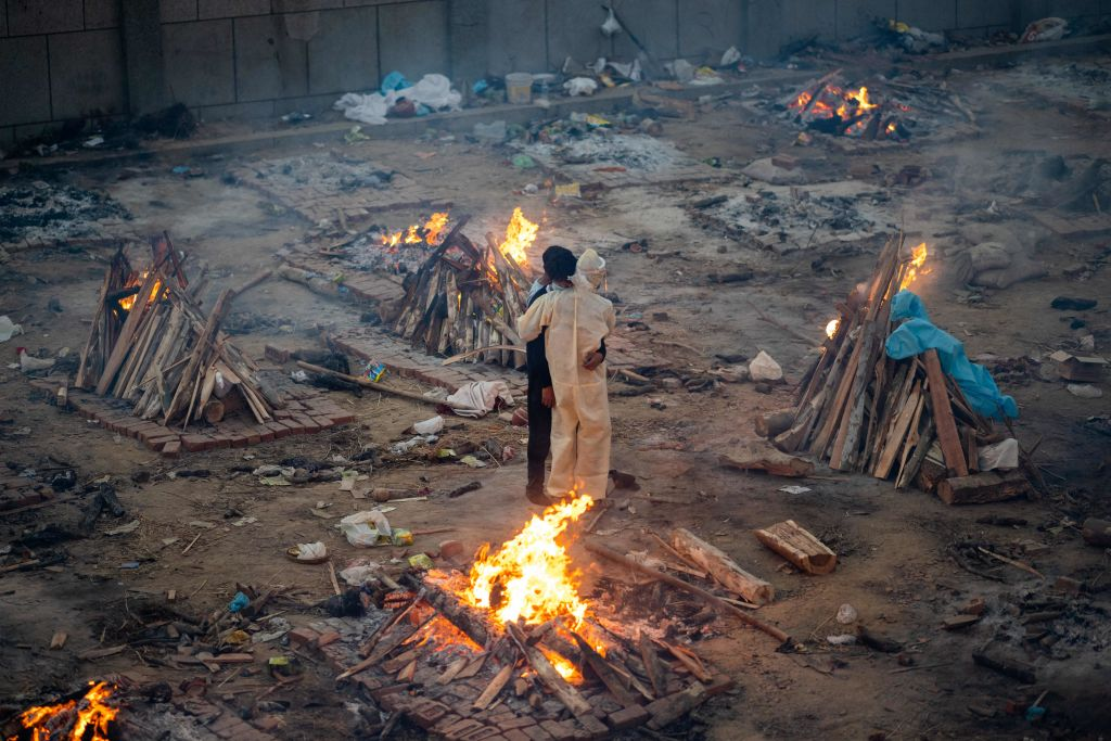 Family members embrace each other amid burning pyres of victims who lost their lives due to the coronavirus at a cremation ground in New Delhi on April 26, 2021.
