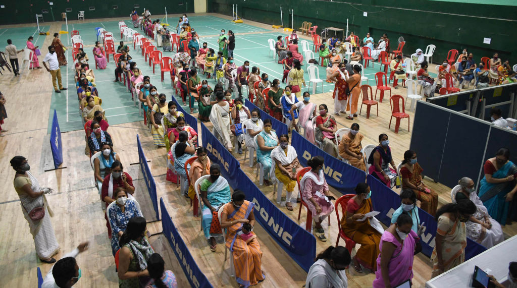 Women line up to receive the COVID-19 vaccine at an indoor stadium in Guwahati, India.