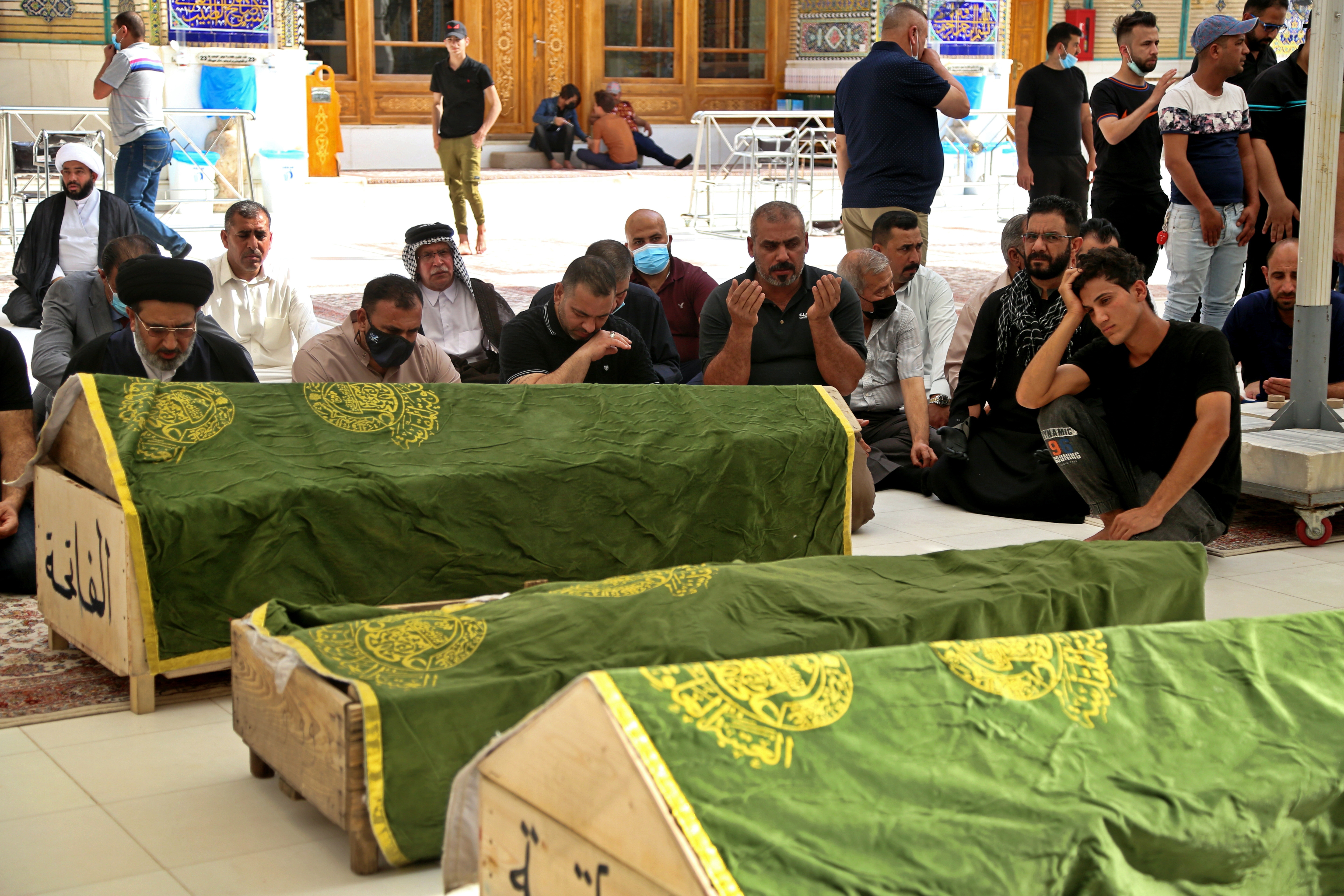 Mourners pray near the coffins of coronavirus patients who were killed in a hospital fire, during their funeral at the Imam Ali shrine in Najaf, Iraq, on April 25, 2021.